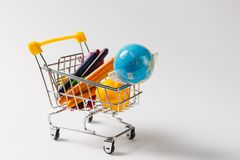 Close up of supermarket grocery push cart for shopping with yellow plastic handle with globe and colored wax pencils royalty free stock photos