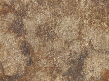 Close up of the surface of a brown and rust coloured rock Stock Images