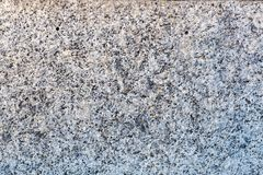 A close-up of a surface of treated grey granite rock plate. A fragment of a stone wall decoration. Texture of bright grey granite facing material royalty free stock photography