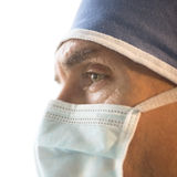 Close-Up Of Surgeon Wearing Surgical Mask And Cap. Close-up of male surgeon wearing surgical mask and cap against white background Stock Image