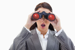 Close-up of a surprised businesswoman looking through binoculars Royalty Free Stock Photo