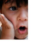 A close up of a surprised little boy. With his hand on his cheek and his mouth open Royalty Free Stock Photo