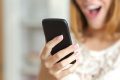 Close up of a surprised woman using a smart phone at home. Close up of a surprised woman hand holding and using a smart phone at home Stock Photo