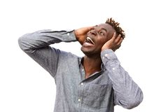 Close up surprised young african man screaming against white wall with hands on face Stock Image