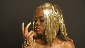 Close-up Surreal Portrait of Glossy African American Woman with Bright Golden Makeup and Headwear. Bronze Bodypaint. Surreal Portrait of Glossy African American stock video