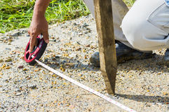 Close-up of a surveyor assistance measuring with measure tape Royalty Free Stock Photos