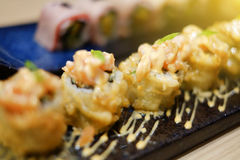 Close up a sushi roll.Fresh and delicious maki.decorate on a black plate in japanese restaurant.selective focus.filtered image. Light effect added Royalty Free Stock Image