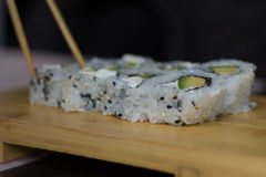 Close-up of sushi rolls. Blurred chopstick taking the food.  Royalty Free Stock Photography