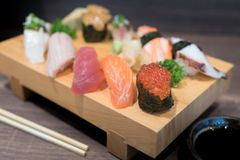 Close-up sushi and sashimi mixed on wooden plate on black wooden Stock Photos