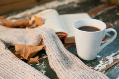 Close up of sweater by open book and coffee cup. On table Stock Photo