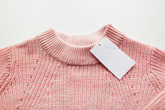 Close up of sweater or pullover with price tag. Clothes, fashion and objects concept - close up of sweater or pullover with price tag on white background Stock Photo