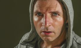 Close up sweaty face portrait of young attractive and fierce looking man wearing hoodie posing in aggressive and defiant attitude. Isolated on dark background stock images