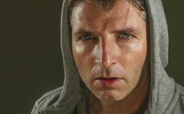 Close up sweaty face portrait of young attractive and fierce looking man wearing hoodie posing in aggressive and defiant attitude stock photography