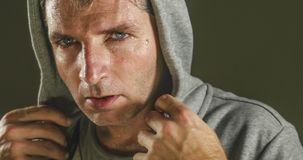 Close up sweaty face portrait of young attractive and fierce looking man wearing hoodie posing in aggressive and defiant attitude. Isolated on dark background royalty free stock images