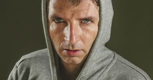 Close up sweaty face portrait of young attractive and fierce looking man wearing hoodie posing in aggressive and defiant attitude. Isolated on dark background stock photography