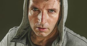 Close up sweaty face portrait of young attractive and fierce looking man wearing hoodie posing in aggressive and defiant attitude royalty free stock image