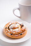 Close up of sweet bun with raisins and cup of coffee over white Royalty Free Stock Photos