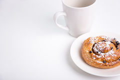 Close up of sweet bun with raisins and cup over white Stock Image