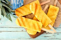 Close up of sweet grilled pineapple wedges against blue wood Royalty Free Stock Photography