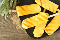 Close up of sweet grilled pineapple wedges on a black plate Royalty Free Stock Images