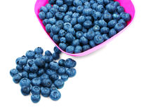 Close-up of sweet juicy blueberries in a bright pink plastic bowl, isolated on a white background. Organic berries for breakfast. Top view of beautiful Stock Image
