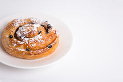 Close up of sweet roll bun with raisins over white Royalty Free Stock Images