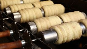 Close up chimney cake baking and rolling. Close up sweet Trdelnik baking on grill and rolling, this spit cake is popular in Europe, Austria, Hungary, Slovakia stock footage
