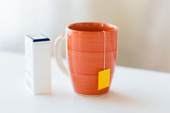 Close up of sweetener and tea cup on table Stock Photo