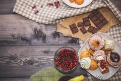 Close-up of sweets on a white plate: coconut pechente, pastila, meringue, cream roses, razat Turkish delight, near a broken royalty free stock images