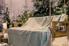 Close up of swing with a blanket and book in a snow-covered park Royalty Free Stock Image