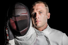 Close-up of swordsman holding fencing mask. Portrait of swordsman holding fencing mask on black background Stock Photos