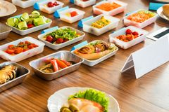 Airplane food presentation with variety of in flight meals. Close up table with bowls of different airplane meals variants at presentation stock photo