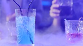 Close-up table with colorful beverages in smoke on background of colored lamps at night stock video