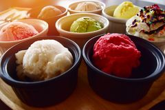 Close Up of table colorful ice cream in small cup placed on tray brown wood. Stock Photos
