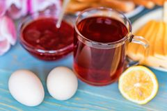 Breakfast with tea, jam and flowers. Close up table with delicious tea, toasts, boiled eggs, cheese, strawberry jam and tulips. Romantic breakfast concept Stock Images