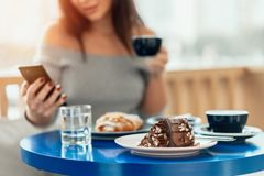 Close up of table with desserts, woman holding cup of coffee and mobile phone. stock images