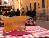 Close-up on a table of an outdoor Italian restaurant. With medieval alley and people walking in the background Stock Photography
