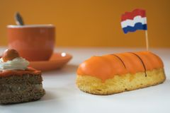 Cup of coffee, orange cake and eclair. Traditional treat for Dutch event Kings Day, Koningsdag royalty free stock photos