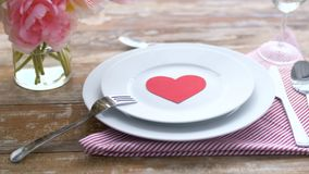 Close up of table setting for valentines day. Valentines day, table setting and romantic dinner concept - close up of plates with red heart shape and cutlery on stock footage