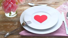 Close up of table setting for valentines day. Valentines day, table setting and romantic dinner concept - close up of plates with red heart shape and cutlery on stock video