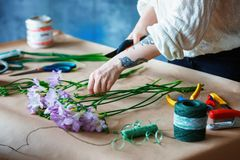 Close up table top view Charming cheerful female shop assistant making bouquet with purple crocus stock photo