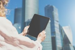 Close-up of a tablet computer with blank screen in female hands against a background of skyscrapers. Mock up. Space for logo Stock Images