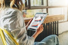 Close-up of tablet computer with charts, graphs, diagrams on screen in hands of young woman sitting in room on chair. Stock Photo