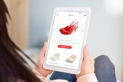 Close-up tablet with eccommerce web site in woman hands. Shoes store concept. Flat design interface stock photography