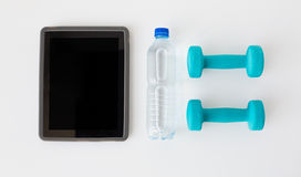 Close up of tablet pc, dumbbells and water bottle Royalty Free Stock Image