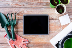 Close up of tablet pc and garden tools on table Royalty Free Stock Images