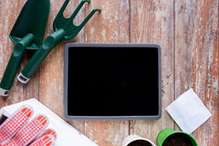 Close up of tablet pc and garden tools on table Royalty Free Stock Photo