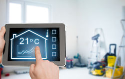Close up of tablet pc in hands setting temperature Stock Image