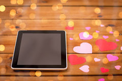 Close up of tablet pc and hearts on wood Royalty Free Stock Image
