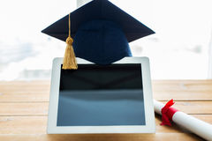 Close up of tablet pc with mortarboard and diploma. Education, graduation, technology and e-learning concept - close up of tablet pc computer with mortarboard Royalty Free Stock Photography